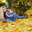 Attractive curly mother and son sitting on the carpet of fallen leaves in a — Stock Photo #13672906