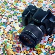 Photo business. SLR camera lying on huge number of digital prin — Stock Photo