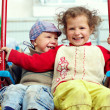 Dirty, happy little gypsy siblings on swings outdoor — Stock Photo