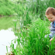Lonely little boy sitting in cane on riverside - Stock Photo