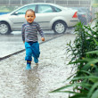 Cute baby boy running under the driving rain — Stock Photo