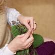 Hands of a young woman knitting with two coloured wool — Stock Photo