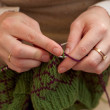 Hands of a young woman knitting with two coloured wool - Stock Photo