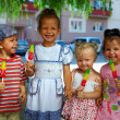 Group of happy kids friends eating fruit ice cream outside — Stock Photo