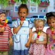 Group of kids siblings eating fruit ice cream outside — Stock Photo