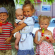 Group of five kids siblings eating fruit ice cream outside — Stock Photo