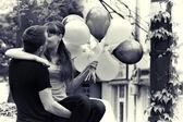 Beso de la pareja de amor, con globos al aire libre — Foto de Stock