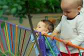 Cute funny little boy biting yummy colorful fence outdoor in kin — Stock Photo
