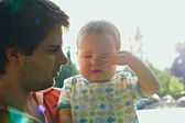 Dad is holding sweet crying son. back-lit with lens flare in the morning — Stock Photo