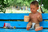 Morning ritual, small baby boy sitting on blue rural bench drinking coffee — Stock Photo