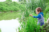 Lonely little boy sitting in cane on riverside, throwing stones — Stock Photo