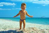Schattige babyjongen lopen van het strand — Stockfoto