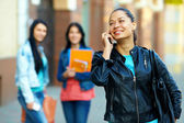 Casual woman talking on the mobile phone, while walking the street — Stock Photo