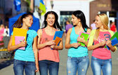 Four beautiful college girls walking on the street — Stock Photo