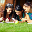 Royalty-Free Stock Photo: Group of happy college girls chatting in social network on green lawn