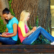 Stock Photo: Two beautiful young girls getting knowledge on bench under old oak tree