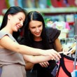 Two happy girls buy dress on store sale — Stockfoto