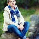 Stylish teenage boy sit on rock, nature outdoors — Stock Photo #13992464