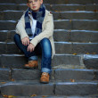 Sad teenage boy sit on stone stairs outdoor — Stock Photo