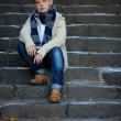 Sad teenage boy sit on stone stairs outdoor — Stock Photo #13992471