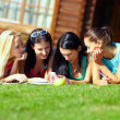 Royalty-Free Stock Photo: Four beautiful girls chatting in social network on green lawn