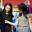 Two happy women shopping in clothes store — Stock Photo #13992486