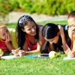 Four beautiful girl having fun outdoors on green lawn — Stock Photo