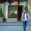 Stylish teenage boy crossing the street of old town — Stok fotoğraf