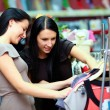 Two happy women shopping in clothes store — Stock Photo #13992502