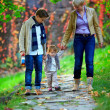 Happy family of three walking the autumn park - Stock Photo