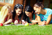 Group of happy college girls chatting in social network on green lawn — Stock Photo