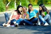 Cztery piękne dziewczyny przyjaciele czytać książki, siedzący na ziemi — Zdjęcie stockowe