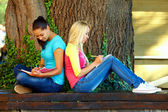 Two beautiful young girls getting knowledge on bench under an old oak tree — Stock Photo