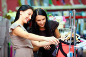 Two happy girls buy dress on store sale — Stock Photo