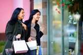 Two excited happy women looking in shop window — Stock Photo