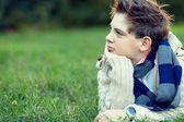 Handsome teenager boy lies on grass and thinks — Stock Photo