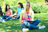 Beautiful female student learns outside on green lawn — Stock Photo