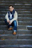 Sad teenage boy sit on stone stairs outdoor — Stock Photo