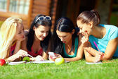 Four beautiful girls chatting in social network on green lawn — Stock Photo