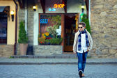 Stylish teenage boy crossing the street of old town — Stock Photo