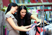 Two happy women shopping in clothes store — Stockfoto