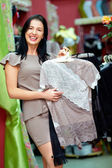 Happy elegant woman shopping in clothing store — Stock Photo