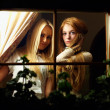 Two beautiful young women looking from window at night — Stock Photo