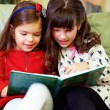 Stock Photo: Two beautiful girls reading book at home