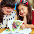 Two beautiful little girls reading book at home — Stok fotoğraf