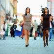 Two elegant women walking the crowded city with shopping bags — Stock Photo