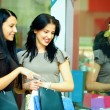 Stock Photo: Two elegant women look in clothes store showcase