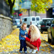 Young mother talking with crying baby boy on city street — Stock Photo