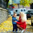 Young mother talking with baby boy on city street — Stock Photo