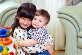 Beautiful little brother and sister embracing in home interior — Stock Photo